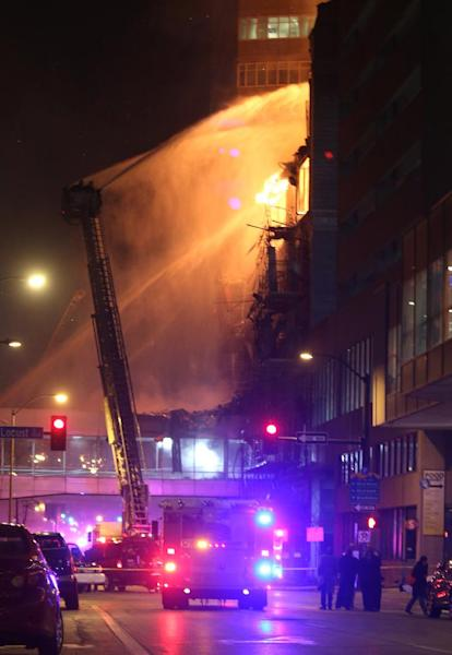 Fire crews from Des Moines work to control a fire at the Younkers building in downtown Des Moines, Iowa early Saturday, March 29, 2014. The massive fire swept through a century-old building that was being renovated, causing its upper floors to collapse and authorities to close down numerous streets in downtown Des Moines. No one was injured. Des Moines Fire Department spokesman Brian O'Keefe said it first got word of a fire at the former Younkers department store building at about 12:50 a.m. Saturday, and arrived to find flames leaping from the upper floors of the seven-floor building, which dates to 1899. (AP Photo/The Des Moines Register, Bryon Houlgrave) MANDATORY CREDIT THE DES MOINES REGISTER BRYON HOULGRAVE