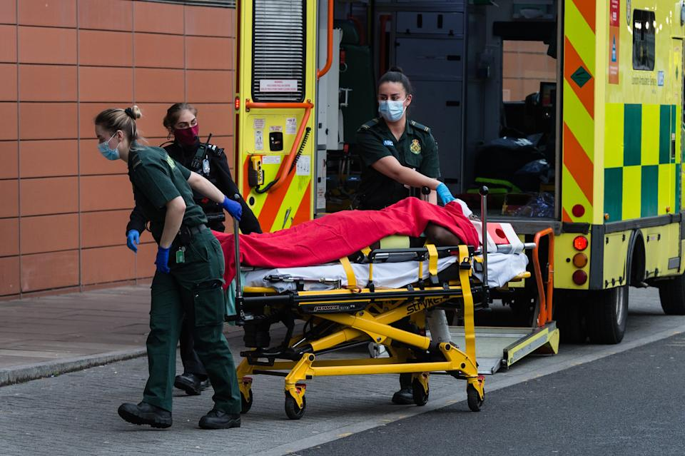 <p>Paramedics take a Covid patient into Royal London Hospital</p> (Getty)