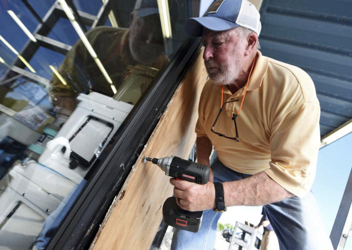 <p>Garland Meadows of Redix boards up the front windows of the store in Wrightsville Beach, N.C., Tuesday, Sept. 11, 2018. (Photo: Matt Born/The Star-News via AP) </p>