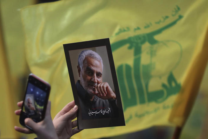 A Hezbollah supporter uses her mobile phone to takes a picture of photo of slain Iranian Revolutionary Guard Gen. Qassem Soleimani during a ceremony marking the anniversary of the assassination of Hezbollah leaders, Abbas al-Moussawi, Ragheb Harb and Imad Mughniyeh and the end of a 40-day Muslim mourning period for Soleimani, in the southern suburb of Beirut, Lebanon, Sunday, Feb. 16, 2020. Nasrallah said U.S. President Donald Trump declared war on the Middle East when the U.S. assassinated Soleimani and when the White House announced its plan to end the Palestinian-Israeli conflict. He called on all to resist U.S. influence and its troops presence. (AP Photo/Hassan Ammar)