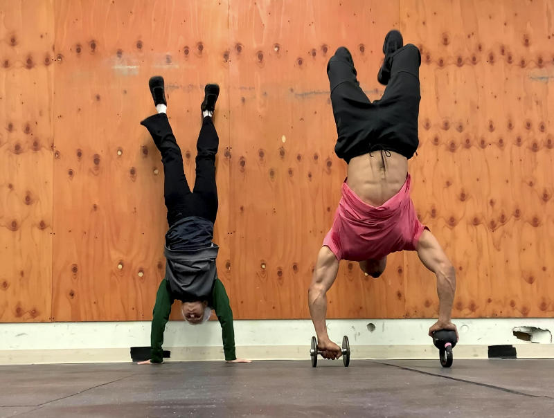 Lauren Bruzzone flipping into a handstand with her trainer. (SWNS)