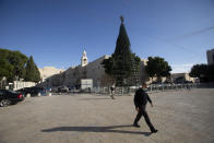 A man walks outside the Church of the Nativity, traditionally believed to be the birthplace of Jesus Christ, in the West Bank City of Bethlehem, Monday, Nov. 23, 2020. Normally packed with tourists from around the world at this time of year, Bethlehem resembles a ghost town – with hotels, restaurants and souvenir shops shuttered by the pandemic. (AP Photo/Majdi Mohammed)