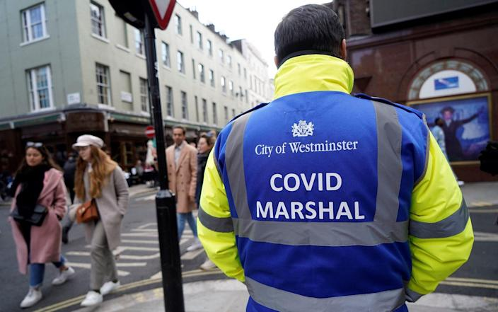 A 'Covid Marshall' from Westminster City Council stands on duty as people drink at re-opened bars in the Soho area of London - NIKLAS HALLE'N/AFP via Getty Images