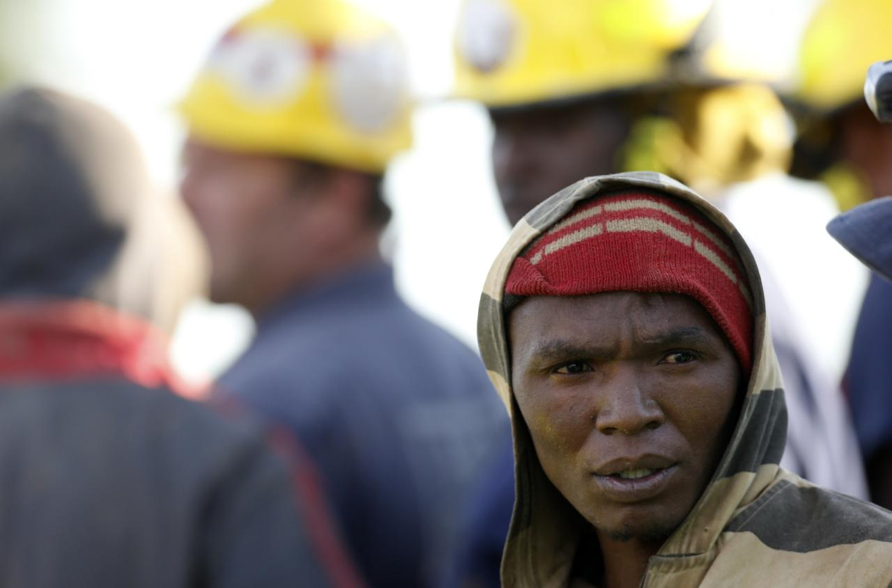 A suspected illegal miner talks to officials after being rescued from an abandoned gold shaft in Benoni, east of Johannesburg, February 16, 2014. South African rescuers started bringing to the surface at least 30 illegal miners on Sunday who had been trapped by debris in the abandoned gold shaft near Johannesburg, emergency services ER24 spokesman Werner Vermaak said. There were no immediate reports of deaths or injuries. Vermaak later told Reuters that some of the miners still underground were refusing to come up, saying they did not want to be arrested. REUTERS/Mike Hutchings (SOUTH AFRICA - Tags: BUSINESS COMMODITIES CRIME LAW DISASTER)