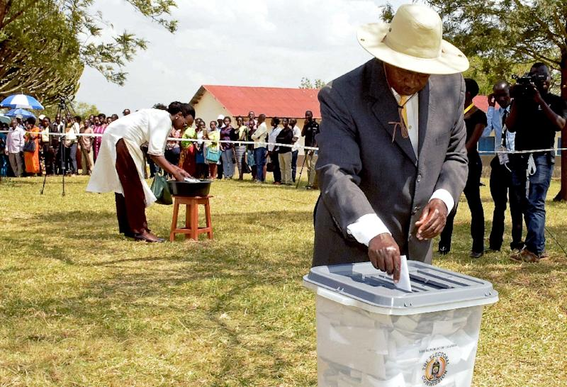 Uganda's President Yoweri Museveni (R) casts his ballot as he votes in parliamentary and presidential elections at a polling station in Nshwere, on February 18, 2016 (AFP Photo/)
