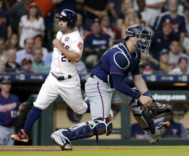 Houston Astros' Jose Altuve (27) scores on a RBI single by Yuli Gurriel as Minnesota Twins catcher Mitch Garver, right, waits for the throw to home plate during the fifth inning of a baseball game Wednesday Sept. 5, 2018, in Houston. (AP Photo/Michael Wyke)