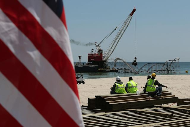 SEASIDE HEIGHTS, NJ - MAY 14: Workers on lunch break watch removal of the Star Jet roller coaster that has been in the ocean for six months after the Casino Pier is sat on collapsed when Superstorm Sandy hit, May 14, 2013 in Seaside Heights, New Jersey. The Casino Pier has contracted Weeks Marine to remove the Jet Star roller coaster from the Atlantic Ocean. (Photo by Mark Wilson/Getty Images)