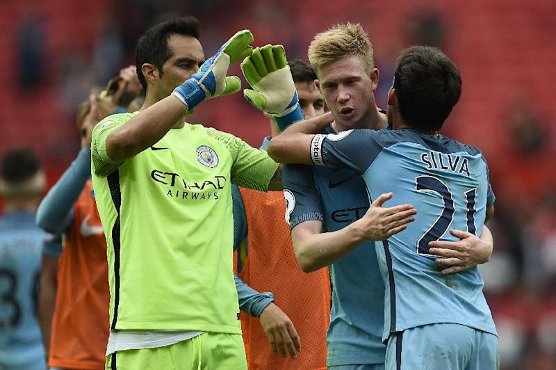 Manchester City midfielder David Silva (R) hugs teammate Kevin De Bruyne as goalkeeper Claudio Bravo joins them after the English Premier League match against Manchester United at Old Trafford in Manchester, north west England, on September 10, 2016 (AFP Photo/Oli Scarff)