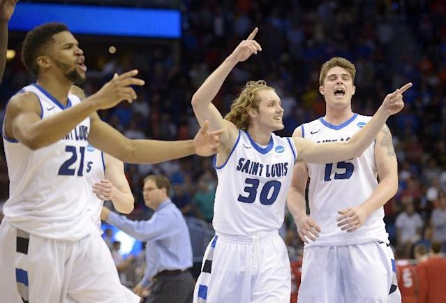 Saint Louis players Dwayne Evans (21), Jake Barnett (30) and Tanner Lancona (15) celebrate their 83-80 overtime win over North Carolina State in a second-round game in the NCAA college basketball tournament Thursday, March 20, 2014, in Orlando, Fla. (AP Photo/Phelan M. Ebenhack)