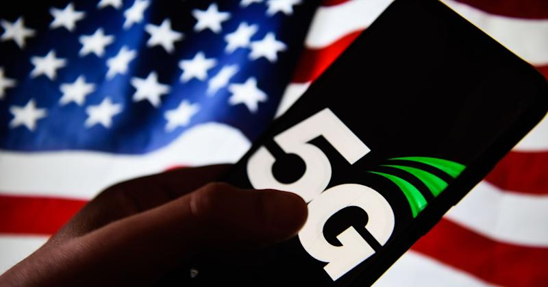 A 5G logo is seen on an android mobile phone with United States of America flag on the background.