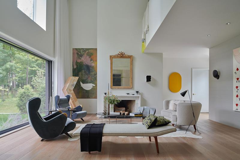 The double-height living area showcases an array of treasures from the couple's collection of art and design, including vintage seating, fourth- and fifth-century pottery, and contemporary works by Al Freeman, Tisch Abelow, and Matt Calderwood, among others.