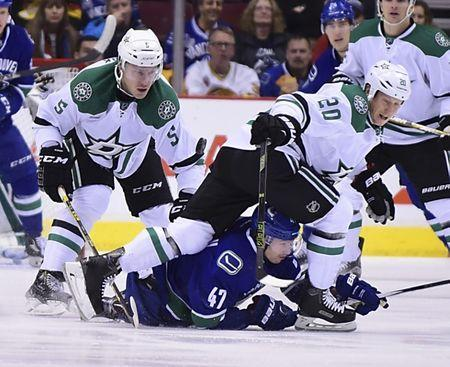 Dec 3, 2015; Vancouver, British Columbia, CAN; Vancouver Canucks forward Sven Baertschi (47) reaches for the puck against Dallas Stars defenseman Jamie Oleksiak (5) and forward Cody Eakin (20) during the first period at Rogers Arena. Mandatory Credit: Anne-Marie Sorvin-USA TODAY Sports / Reuters Picture Supplied by Action Images