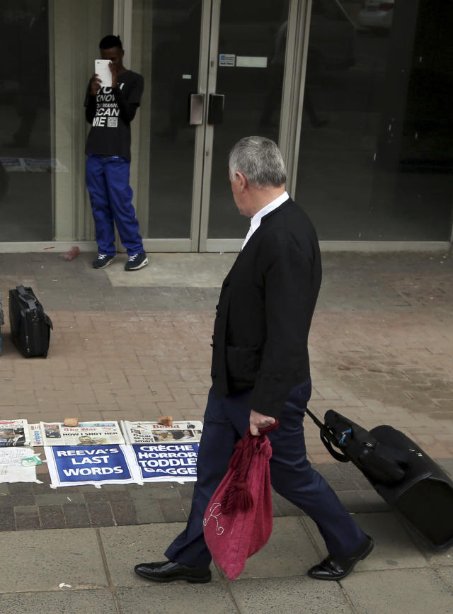 Barry Roux, the lawyer defending Oscar Pistorius, walks past newspaper headlines outside the high court in Pretoria, South Africa, Wednesday, April 9, 2014. Pistorius is charged with murder for the shooting death of his girlfriend Reeva Steenkamp on Valentine's Day in 2013. (AP Photo/Themba Hadebe)