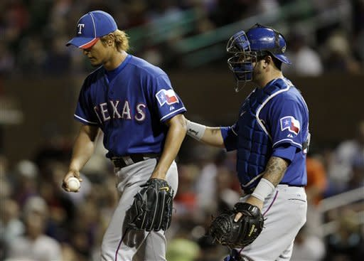 Texas Rangers starting pitcher Yu Darvish, left, gets a visit to the mound from catcher Mike Napoli against the Colorado Rockies during the sixth inning of a spring training baseball game Friday, March 30, 2012 in Scottsdale, Ariz. (AP Photo/Marcio Jose Sanchez)