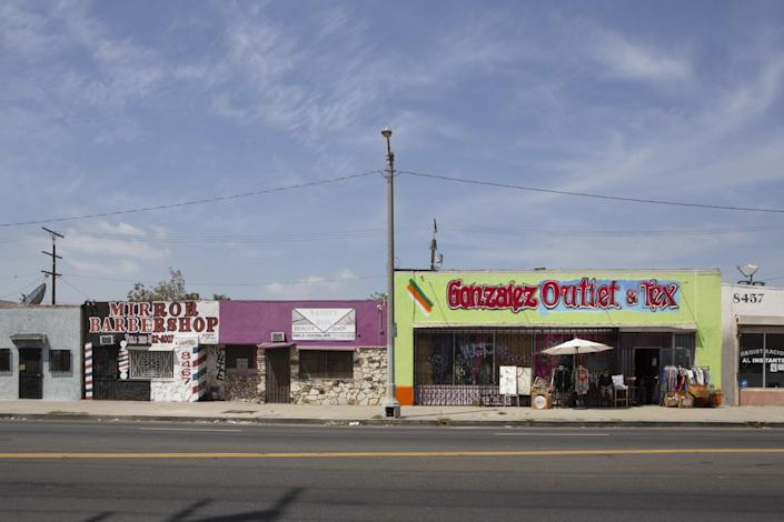 Storefronts on an empty street include Mirror Barbershop and Gonzalez Outlet