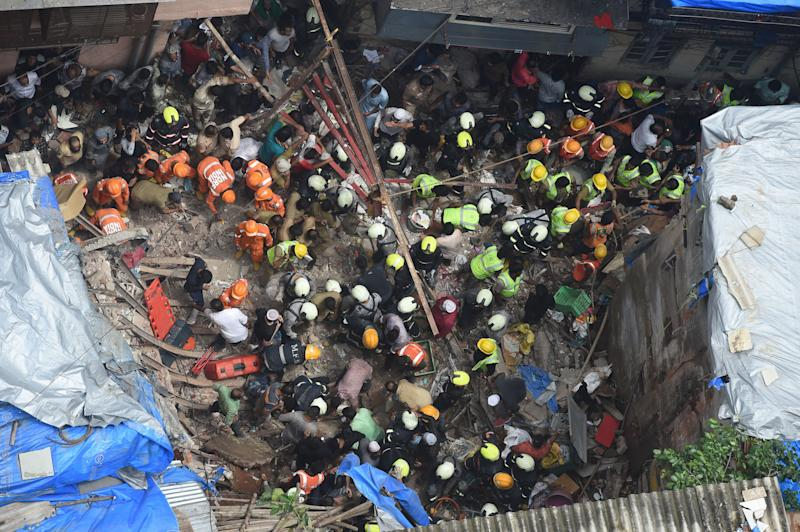 Fire brigade personnel and rescue workers look for survivors after a building collapsed in Mumbai on July 16, 2019. (Photo: PUNIT PARANJPE via Getty Images)