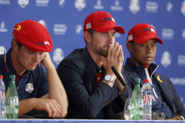 US players Bryson Dechambeau, left, Webb Simpson, center, and Tiger Woods attend the press conference of the losing team after Europe won the 2018 Ryder Cup golf tournament at Le Golf National in Saint Quentin-en-Yvelines, outside Paris, France, Sunday, Sept. 30, 2018. (AP Photo/Alastair Grant)