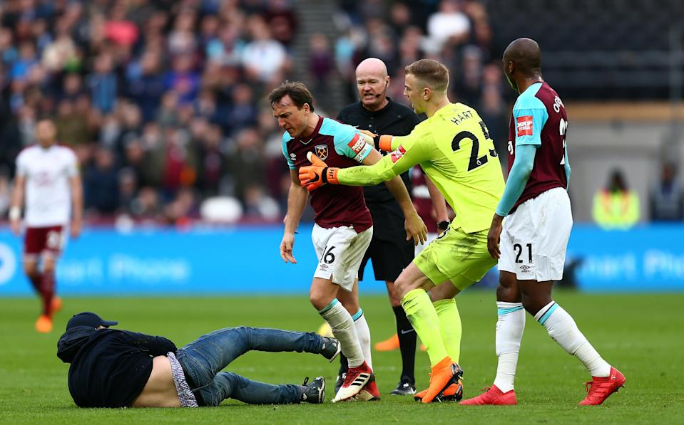 Mark Noble clashes with a West Ham fan who had invaded the pitch. (Getty)