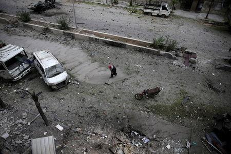 A man cleans up a damaged site after what activists said was shelling by forces loyal to Syria's President Bashar al-Assad in the Douma neighborhood of Damascus, Syria November 22, 2015. Picture taken November 22, 2015. REUTERS/Bassam Khabieh