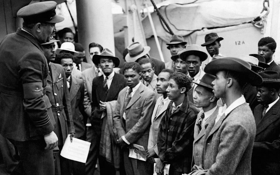 Jamaican immigrants are welcomed by RAF officials from the Colonial Office after the ex-troopship HMT Empire Windrush brought them to Tilbury, in Essex - PA