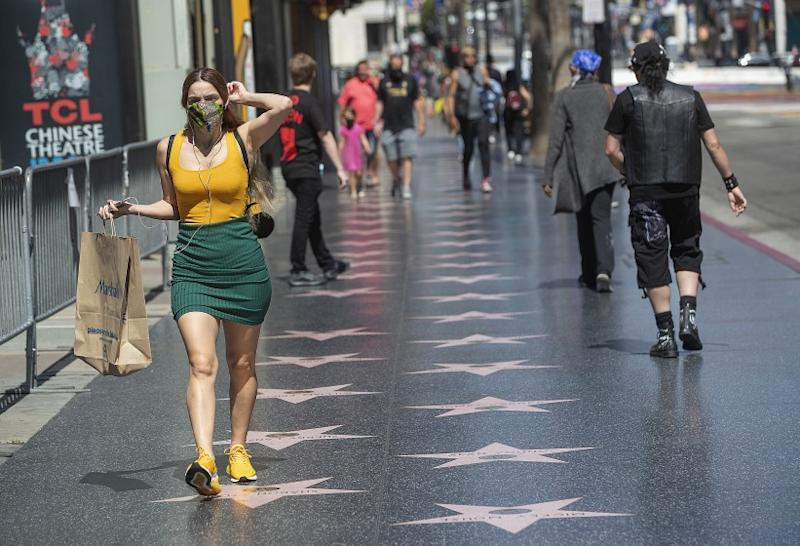 HOLLYWOOD, CA-JUNE 18, 2020-A pedestrian adjusts her face covering while walking along Hollywood Blvd. in Hollywood. Gov. Gavin Newsom on Thursday ordered all Californians to wear face coverings while in public, following growing concerns that an increase in coronavirus cases has been caused by residents failing to voluntarily take that precaution. (Mel Melcon/Los Angeles Times)