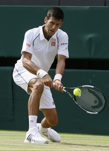 Novak Djokovic of Serbia returns a ball to Bernard Tomic of Australia during their singles match at the All England Lawn Tennis Championships in Wimbledon, London, Friday July 3, 2015. (AP Photo/Kirsty Wigglesworth)