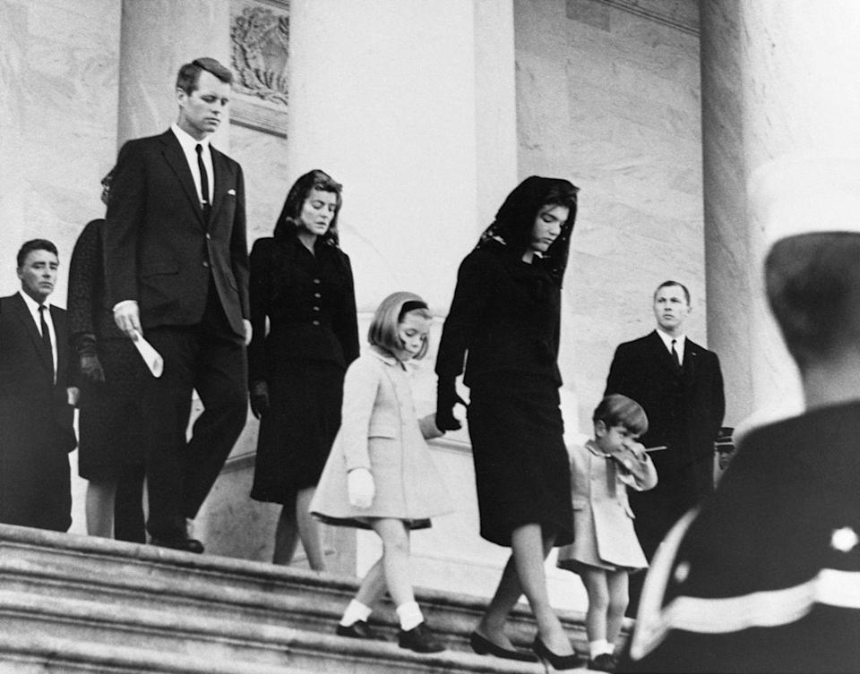 <p>Jacqueline Kennedy, with John Jr. and Caroline, leaves the White House for a service at the Capitol honoring her slain husband.</p>