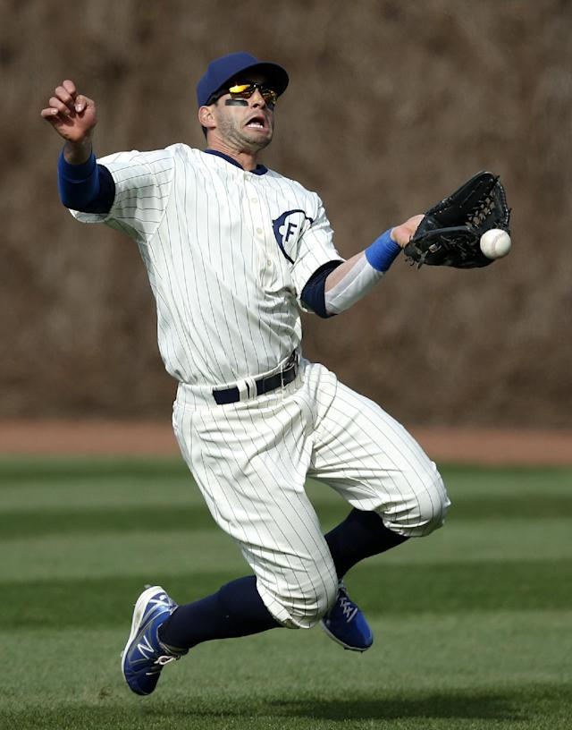Chicago Cubs right fielder Justin Ruggiano misses the catch on a triple by Arizona Diamondbacks' Aaron Hill, on which two runs scored during the ninth inning of a baseball game at Wrigley Field in Chicago on Wednesday, April 23, 2014. (AP Photo/Andrew A. Nelles)