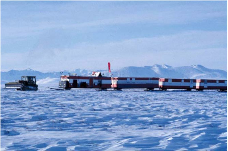 A tractor pulling ski-mounted camp trailers in the 1002 area of the Arctic National Wildlife Refuge during seismic exploration in February 1984. (US Fish and Wildlife Service)