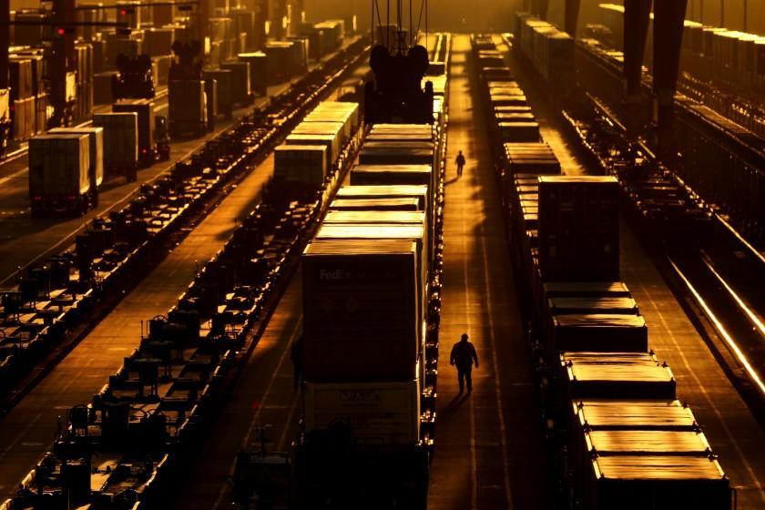 Workers walk along the tracks at an intermodal facility as the sun sets Monday, Dec. 21, 2020, in Edgerton, Kan. The facility, operated by BNSF railway, transfers shipping containers between rail cars to trucks. (AP Photo/Charlie Riedel)