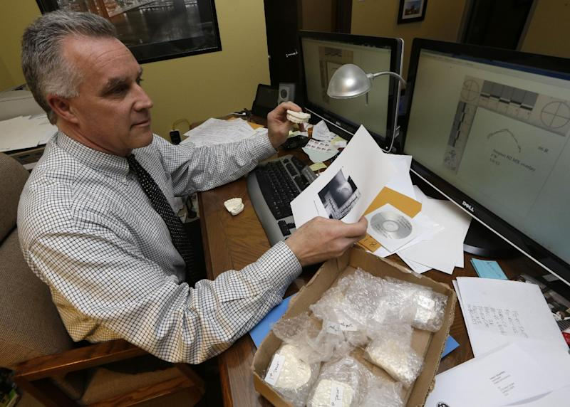 This photo made Thursday, March 28, 2013, in Cincinnati, shows Dr. Frank Wright, a forensic dentist, studying evidence in a bite mark analysis, which he practices on a regular basis in between seeing patients at his office and conducting research on different ways of photographing bite marks. (AP Photo/Al Behrman)