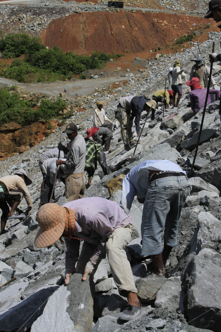 In this Oct. 6, 2012 photo, local workers pile stones at a dam construction site by China National Heavy Machinery Corporation on the Tatay River in Koh Kong province, some 210 kilometers (130 miles) west of Phnom Penh, Cambodia. Up a sweeping, jungle valley in a remote corner of Cambodia, Chinese engineers and workers are raising a 100-meter- (330-foot) high dam over the protests of villagers and activists. Only Chinese companies are willing to tame the Tatay and other rivers of Koh Kong province, one of Southeast Asia's last great wilderness areas. (AP Photo/Heng Sinith)