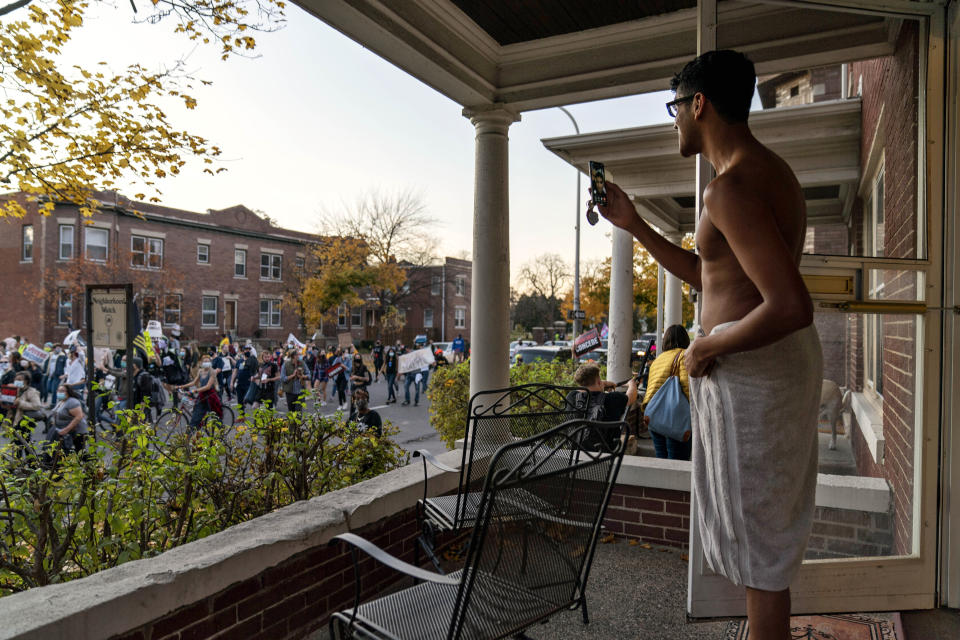 Karthik Mantha stands on his front porch wearing a towel, just as he was about to step into a shower, to watch a rally pass by celebrating the presidential election results in Detroit, Saturday, Nov. 7, 2020. (AP Photo/David Goldman)