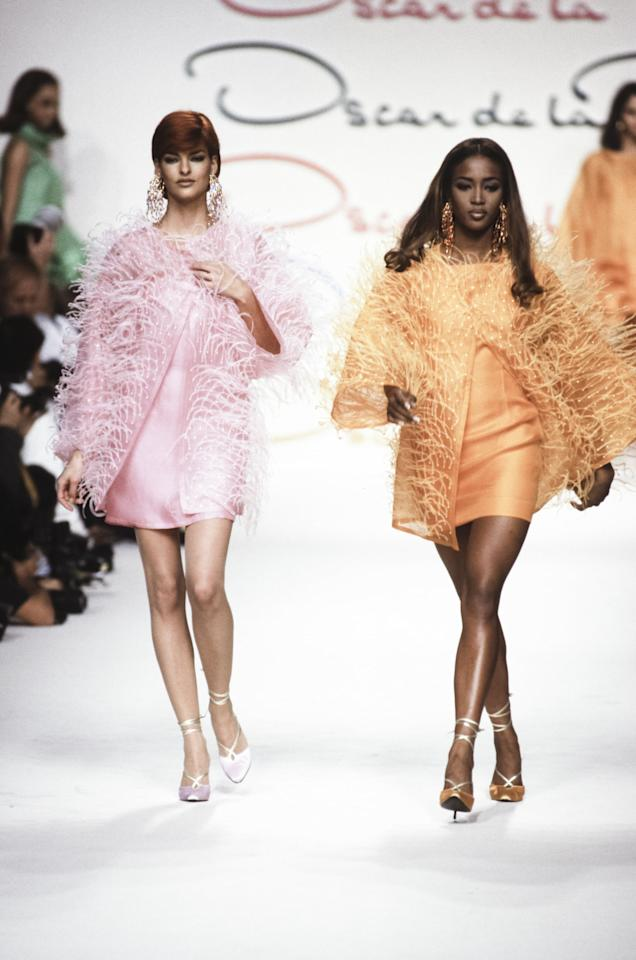 """<p><a class=""""sugar-inline-link ga-track"""" title=""""Latest photos and news for Naomi Campbell"""" href=""""https://www.popsugar.com/Naomi-Campbell"""" target=""""_blank"""" data-ga-category=""""Related"""" data-ga-label=""""https://www.popsugar.com/Naomi-Campbell"""" data-ga-action=""""&lt;-related-&gt; Links"""">Naomi Campbell</a> and Linda Evangelista walking in Oscar de la Renta in 1991</p>"""