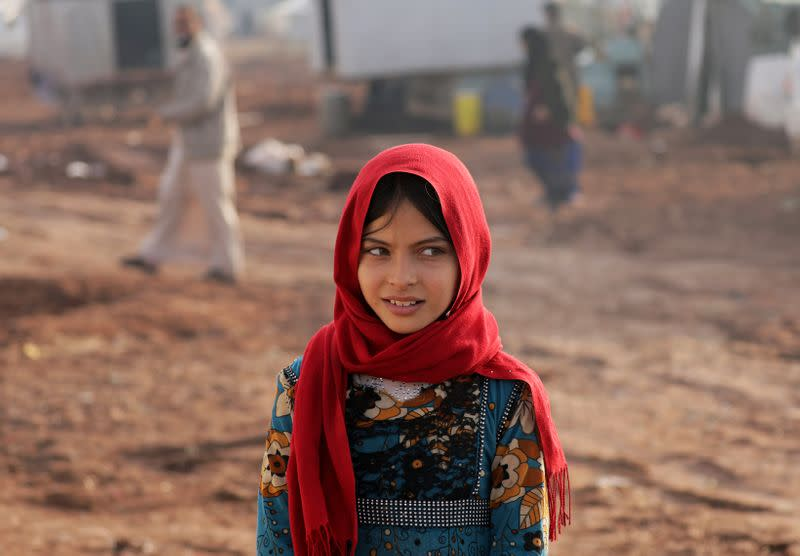 An internally displaced girl poses for a picture at a makeshift camp in Azaz