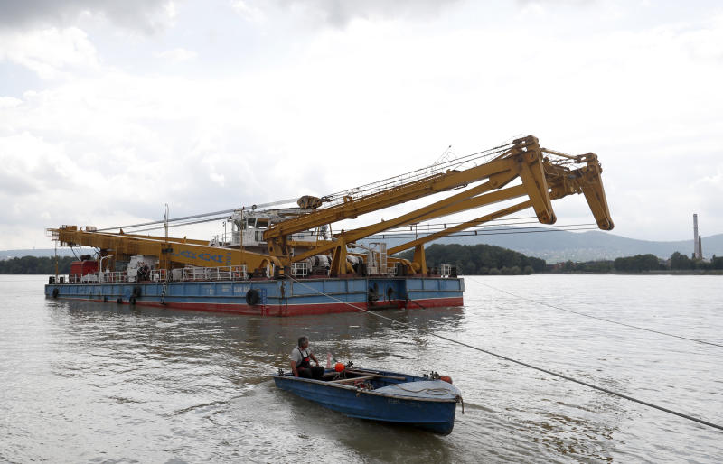 A floating crane able to lift 200 tons and which would be able to hoist the boat out of the water on its way on the site of the accident where a sightseeing boat capsized in Budapest, Hungary, Wednesday, June 5, 2019. South Korean officials say divers in Budapest have begun preparing a sunken tour boat in the hope that a huge floating crane can lift it out of the Danube River. (AP Photo/Laszlo Balogh)