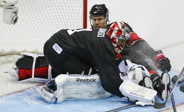 Canada goaltender Roberto Luongo smothers the puck on a rebound in the third period of a men's ice hockey game against Austria at the 2014 Winter Olympics, Friday, Feb. 14, 2014, in Sochi, Russia. (AP Photo/Julio Cortez)