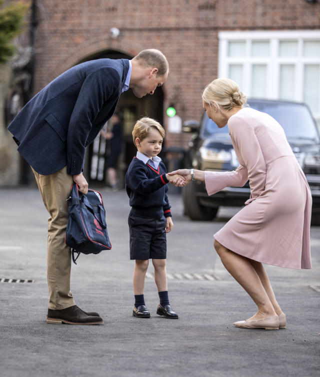 Prince William walks Prince George to his first day of school, where they were greeted by a teacher. (Photo: Getty Images)