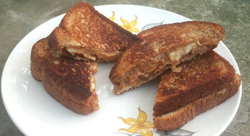 Four peanut butter banana bacon sandwich triangles fried golden brown and stacked on a plate