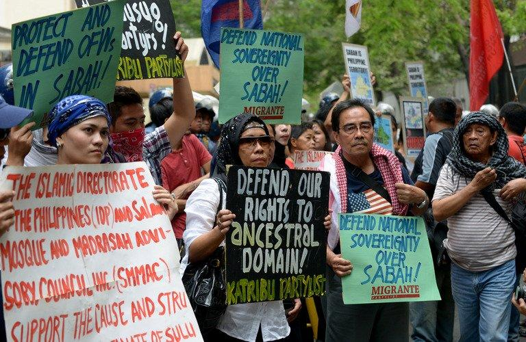 Protesters hold placards as they attend a rally in front of the Malaysian embassy in Manila on March 5, 2013