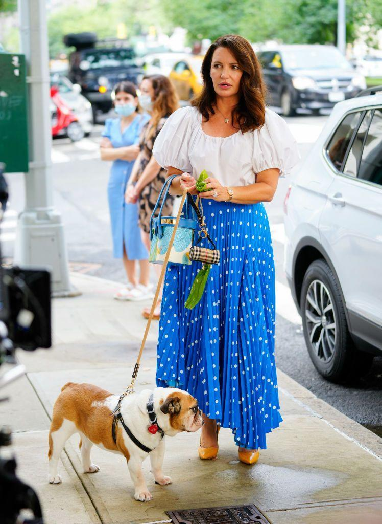 """<p>Seen filming a walking-a-dog segment on the streets of New York City, Davis did so carrying the<a href=""""https://riannaandnina.com/collections/treasure-box/products/the-treasure-box-2"""" rel=""""nofollow noopener"""" target=""""_blank"""" data-ylk=""""slk:Rianna and Nina treasure box bag"""" class=""""link rapid-noclick-resp""""> Rianna and Nina treasure box bag</a>, which was handcrafted in Milan and costs €5,210 (£4,437) to buy. </p><p>According to must-follow Instagram page, @everyoutfitonsatc Charlotte's white blouse is Stella McCartney and polka dot blue asymmetric skirt is Balenciaga - which is still available to buy:</p><p><a class=""""link rapid-noclick-resp"""" href=""""https://www.net-a-porter.com/en-gb/shop/product/balenciaga/belted-asymmetric-pleated-polka-dot-crepe-midi-skirt/1238359"""" rel=""""nofollow noopener"""" target=""""_blank"""" data-ylk=""""slk:SHOP NOW"""">SHOP NOW</a> Belted asymmetric pleated polka-dot crepe midi skirt, £990<br></p><p>NB: Seemingly now the owner of a bulldog rather than Elizabeth Taylor the spaniel, Charlotte was also seen carrying a Burberry poo bag dispense.</p>"""