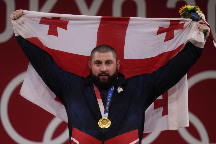 Lasha Talakhadze of Georgia holds his national flag as he celebrates the gold medal he won at the men's +109kg weightlifting event, at the 2020 Summer Olympics, Wednesday, Aug. 4, 2021, in Tokyo, Japan.(AP Photo/Luca Bruno)