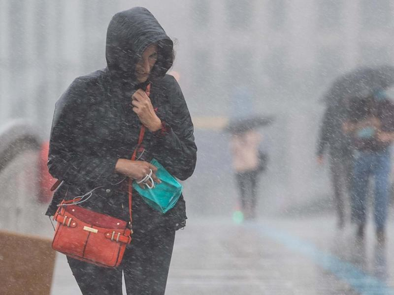 A woman runs to take shelter from a heavy downpour of rain on London Bridge, in central London: PA
