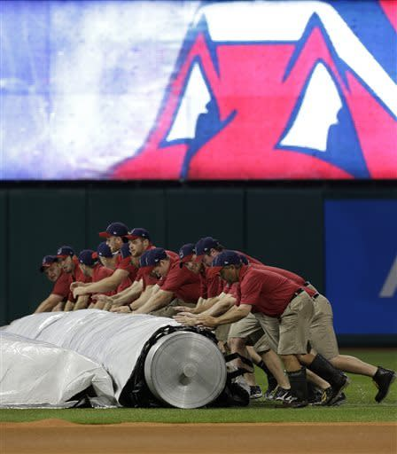The Cleveland Indians ground crew roll up the tarp during a rain delay in a baseball game between the Indians and the Detroit Tigers, Wednesday, May 22, 2013, in Cleveland. (AP Photo/Tony Dejak)