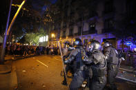Policemen in riot gear charge against protestors outside the Spanish Government Office in Barcelona, Spain, Tuesday, Oct. 15, 2019. Spain's Supreme Court on Monday convicted 12 former Catalan politicians and activists for their roles in a secession bid in 2017, a ruling that immediately inflamed independence supporters in the wealthy northeastern region. (AP Photo/Emilio Morenatti)