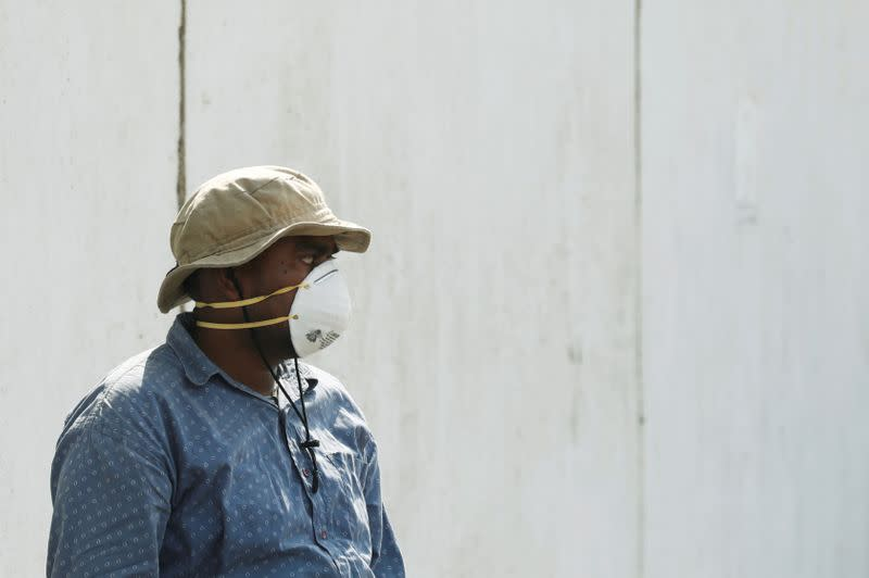 FILE PHOTO: A man wearing a face mask waits to see a relative who is admitted after being affected from a suspected gas leak, at a hospital premises in Karachi