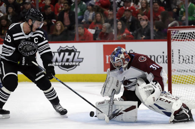 Colorado Avalanche goalie Philipp Grubauer, right, blocks a shot by Chicago Blackhawks center Jonathan Toews during the second period of an NHL hockey game Sunday, March 24, 2019, in Chicago. (AP Photo/Nam Y. Huh)