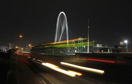 A bus passes in front of the Margaret Hunt Hill Bridge in Dallas, Texas