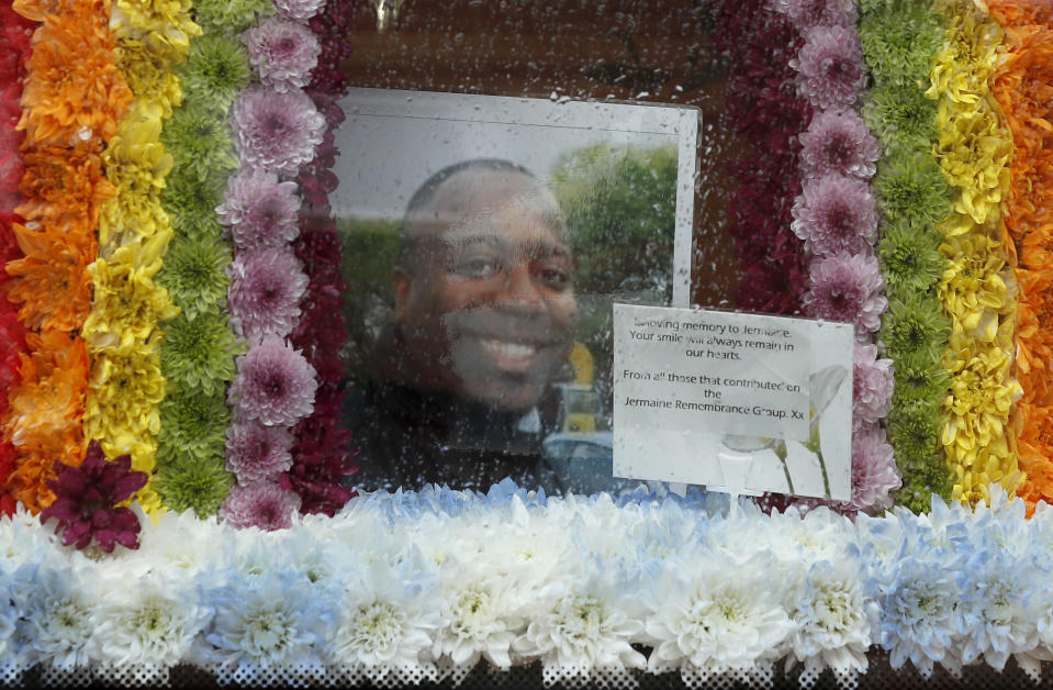 A picture of Jermaine Wright, a referee of the Hackney Marshes grassroots football league who died of COVID-19, is placed in a rainbow of flowers inside the hearse in front of his house in London, Thursday, June 11, 2020. The deadly coronavirus has killed thousands of people in Britain, but each death is not just a number and is deeply personal for each family.(AP Photo/Frank Augstein)