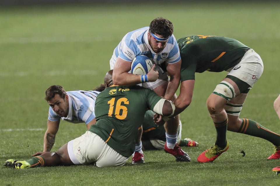 Julian Montoya of Argentina, center, is tackled by Bongi Mbonambi of South Africa during the second Rugby Championship match between Argentina and South Africa at the Nelson Mandela Bay Stadium, Gqebeha, South Africa, Saturday, Aug. 21, 2021. (AP Photo/Halden Krog)
